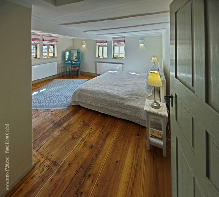 The master bedroom has a king sized bed and a wardrobe.